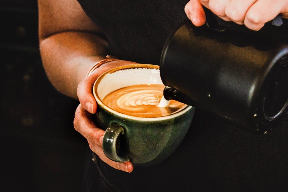person pouring cappuccino on gray mug