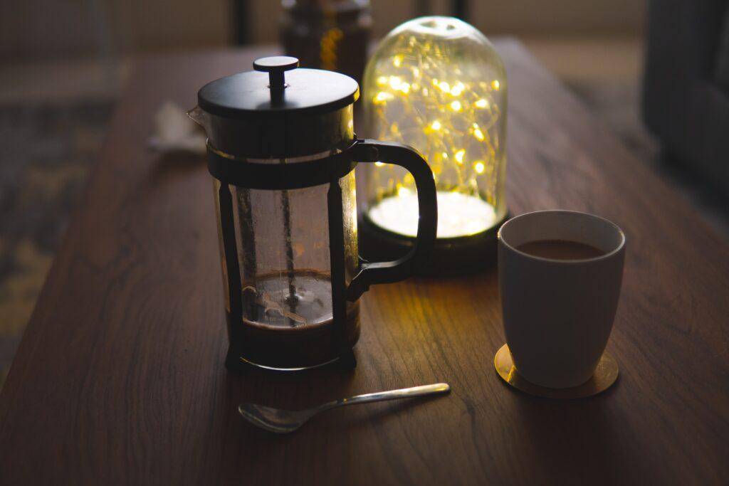 white ceramic mug beside black coffee press on brown wooden table