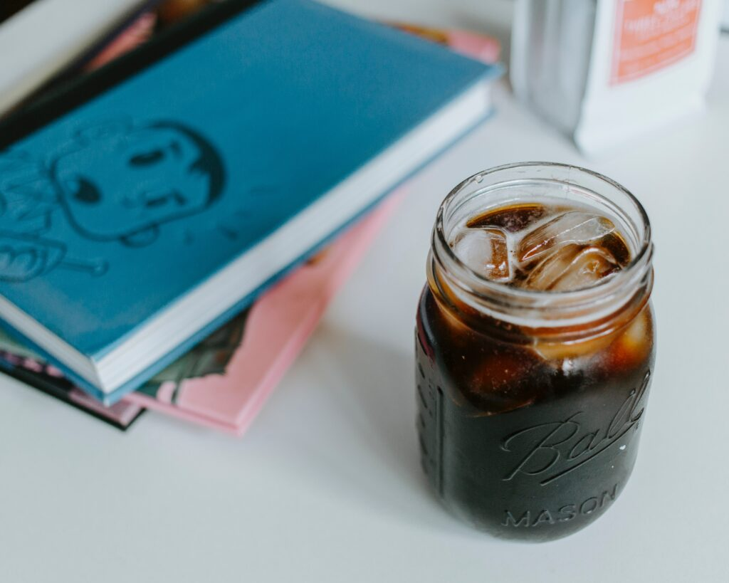 clear glass mason jar with cola and ice cubes on table near notebooks